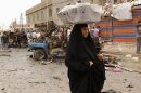 An Iraqi woman, who sells milk, passes by the scene of a car bomb attack in the Kamaliyah neighborhood, a predominantly Shiite area of eastern Baghdad, Iraq, Monday, May 20, 2013. A wave of car bombings across Baghdad&#039;s Shiite neighborhoods and in the southern city of Basra killed and wounded scores of people, police said. (AP Photo/ Hadi Mizban)