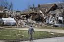 A soldier walks past the wreckage left when a tornado moved through Moore, Okla., Tuesday, May 21, 2013. The huge tornado roared through the Oklahoma City suburb, flattening entire neighborhoods and destroying an elementary school with a direct blow as children and teachers huddled against winds.(AP Photo/Brennan Linsley)