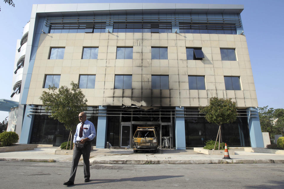A security guard walks outside Microsoft's offices in northern Athens, Wednesday, June 27, 2012. Assailants attacked the offices of Microsoft early Wednesday, driving a van through the front doors and setting off an incendiary device that burned the building entrance, police said. (AP Photo/Thanassis Stavrakis)