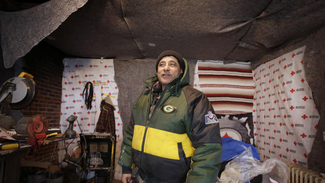 Eddie Saman shows off his home which he has insulated with blankets donated by the Red Cross, Wednesday, Jan. 23, 2013 in the borough of Staten Island in New York. The house was badly damaged by Superstorm Sandy and will have to be renovated. Meanwhile, because of the extreme cold weather, Saman has been spending the night in a tent nearby operated by the volunteer group Cedar Grove Community Hub.   (AP Photo/Mark Lennihan)