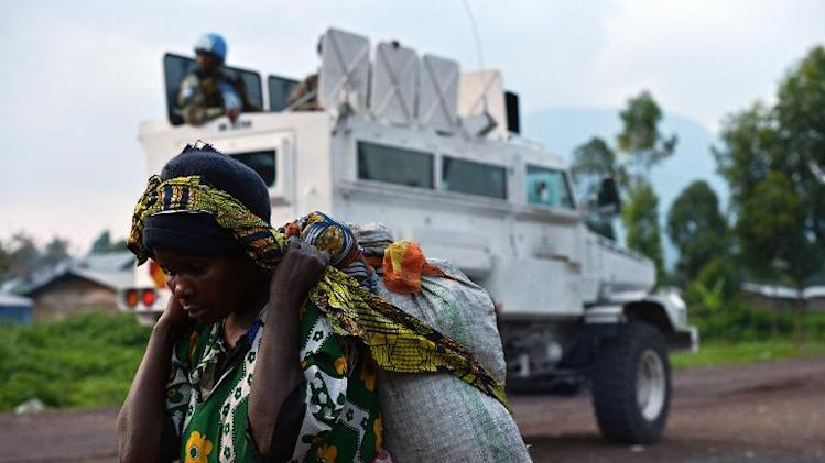 A Congolese woman walks past an armoured vehicle of MONUSCO near Kibati, close to Goma on September 4, 2013
