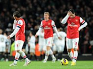 Arsenal's Mikel Arteta (R) reacts after Swansea scored a goal during the English Premier League match at the Emirates Stadium in north London, on December 1. Swansea won 2-0