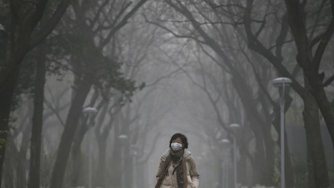 A woman wearing a mask walks as smog covers China's capital Beijing