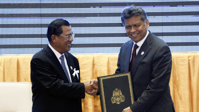 Cambodia's Prime Minister Hun Sen, left, shakes hands with ASEAN Secretary-General Surin Pitsuwan as Hun Sen handed over a signed document to Surin after the singing ceremony of adoption of the ASEAN Human Rights Declaration during the 21st Association of Southeast Asian Nations, or ASEAN Summit in Phnom Penh, Cambodia, Sunday, Nov. 18, 2012. (AP Photo/Vincent Thian)