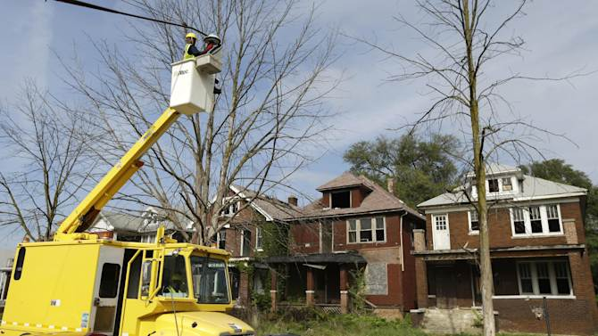 In a Sept. 25, 2013 photo, Leonard Robinson checks a lighting fixture in west Detroit. A new light would draw a yawn in most cities, but it means real progress in Detroit, which is providing services residents hadn't seen in years while attempting to turn itself around in bankruptcy court. (AP Photo/Carlos Osorio)