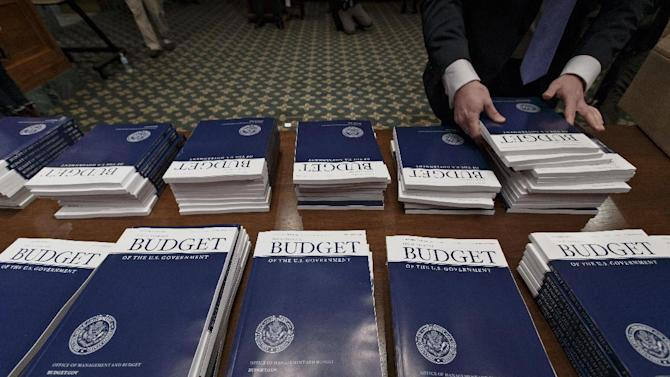 Copies of President Barack Obama's proposed fiscal 2015 budget are set out for distribution by Senate Budget Committee Clerk Adam Kamp, on Capitol Hill in Washington, Tuesday, March 4, 2014. President Barack Obama is unwrapping a nearly $4 trillion budget that gives Democrats an election-year playbook for fortifying the economy and bolstering Americans' incomes. It also underscores how pressure has faded to launch bold, new attacks on federal deficits. (AP Photo/J. Scott Applewhite)