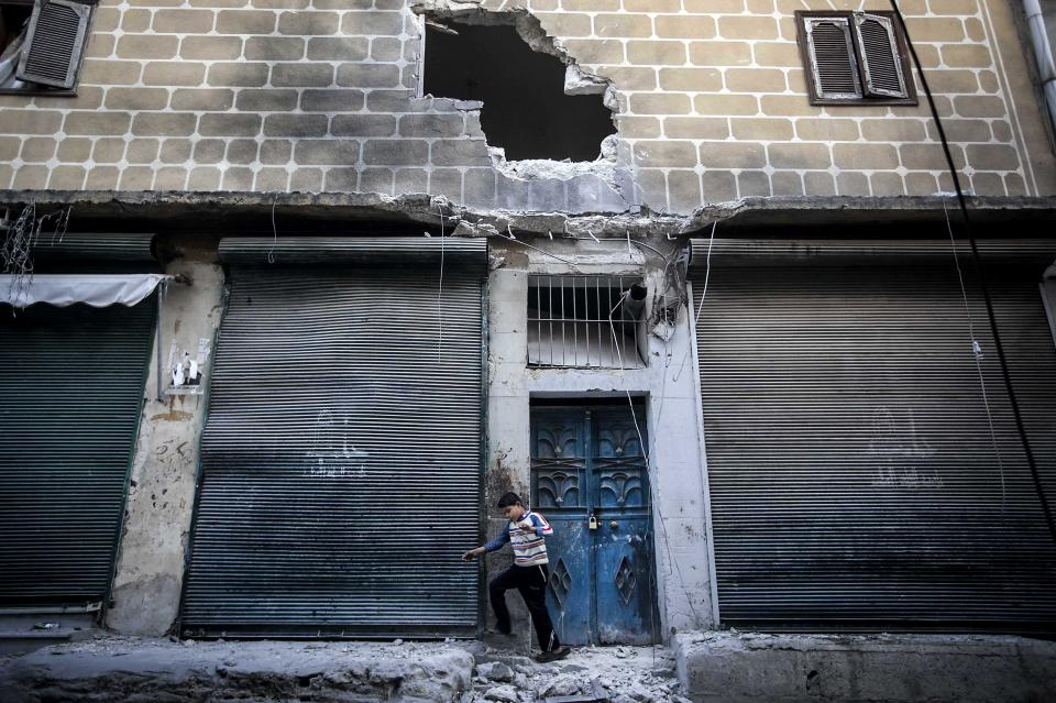 In this Sunday, Dec. 2, 2012 photo, a boy walks past a bakery damaged from a mortar shell during heavy fighting between Free Syrian Army fighters and government forces in Aleppo, Syria. (AP Photo/Narciso Contreras)