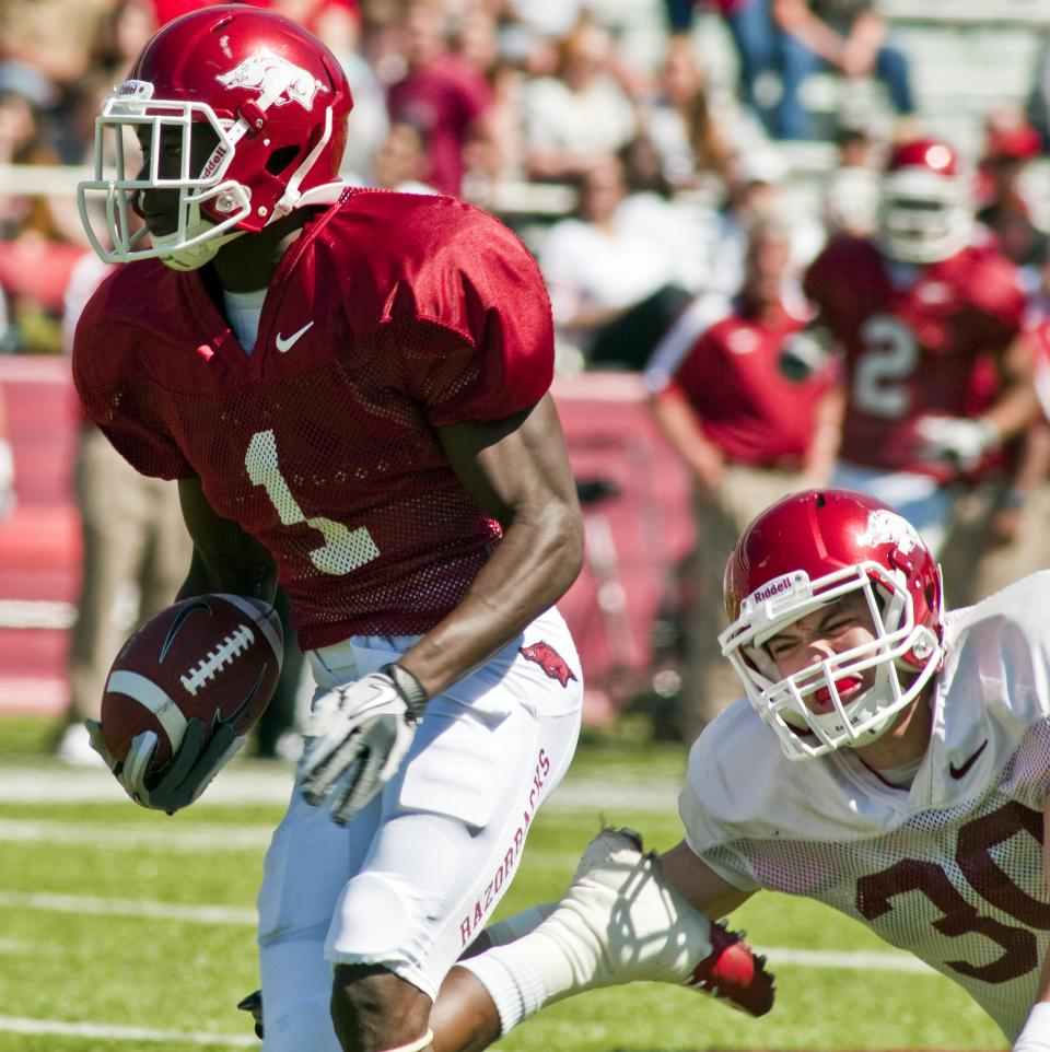 Arkansas red team receiver Marquel Wade (1) runs down field after making a catch as white team safety Houston Pruitt (30) reaches in to trip him up during the second quarter of a spring NCAA college football game in Fayetteville, Ark., Saturday, April 21, 2012. (AP Photo/April L. Brown)