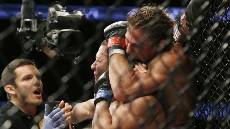 Ivan Menjivar, center, taps out as he is choked by Urijah Faber, right, during their UFC 157 bantamweight mixed martial arts match in Anaheim, Calif., Saturday, Feb. 23, 2013. At left is referee Jason Herzog. (AP Photo/Jae C. Hong)