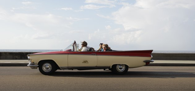 Tourists ride a U.S.-made convertible car on Havana's seafront boulevard 'El Malecon'