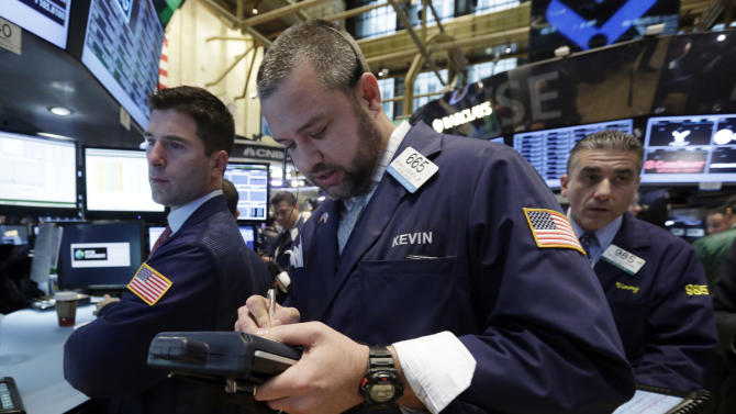 In this Dec. 19, 2013 photo, trader Kevin Lodewick, center, works on the floor of the New York Stock Exchange. World stocks traded higher on Monday, Dec. 23, 2013, despite concerns over a cash crunch in China as investor sentiment remained buoyed by growing optimism over the U.S. economy. (AP Photo/Richard Drew)