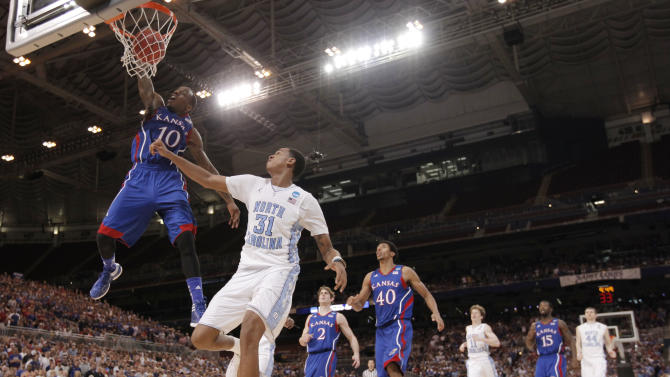 Kansas guard Tyshawn Taylor (10) duns against North Carolina forward John Henson (31) during the second half of the NCAA men's college basketball tournament Midwest Regional final Sunday, March 25, 2012, in St. Louis. Kansas won 80-67. (AP Photo/Charlie Riedel)