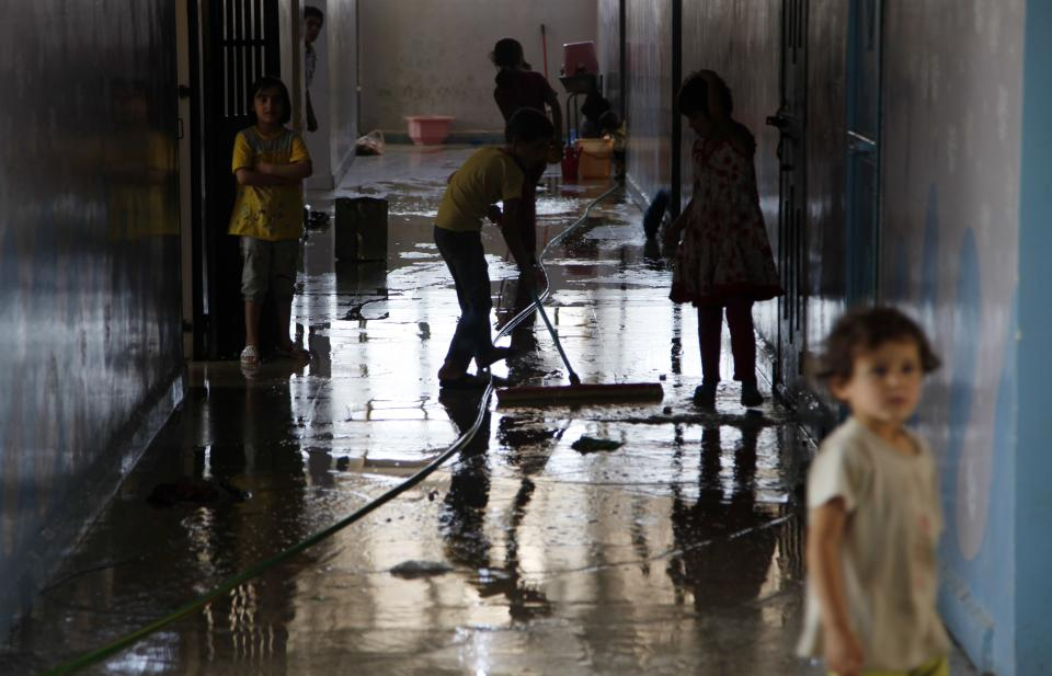 Syrian children clean a school where they live with their families after they have fled the fighting in surrounding areas in town of Kafr Hamra some ten kilometers (six miles)  north of the center of  Aleppo city, Syria, Tuesday, Aug. 7, 2012. (AP Photo/ Khalil Hamra)