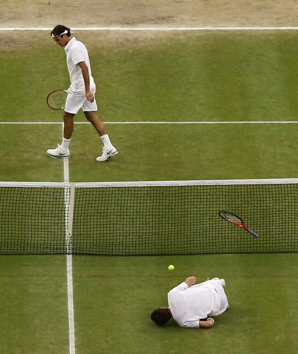 Andy Murray of Britain, front, takes a fall during the men's singles final match against  Roger Federer of Switzerland at the All England Lawn Tennis Championships at Wimbledon, England, Sunday, July