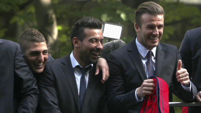 Paris Saint Germain's soccer players Marco Verratti, left, Ezequiel Lavezzi, center,  and David Beckham, right, celebrate winning their French league, in Paris, Monday, May 13, 2013. Paris Saint-Germain clinched its first French league title since 1994 by defeating Lyon 1-0 on Sunday. PSG has now an unassailable seven-point lead at the top of the standings. With just two rounds left, second-place Marseille can no longer catch its fierce rival. (AP Photo/Thibault Camus)