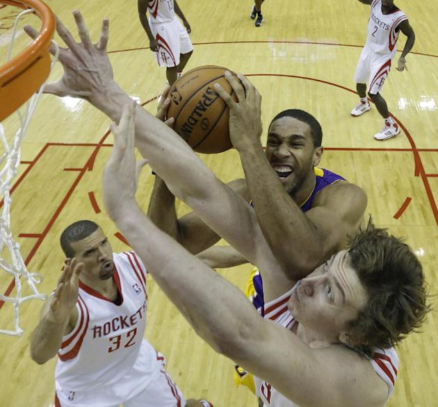Los Angeles Lakers' Xavier Henry, top, goes up for a shot as Houston Rockets' Omer Asik, bottom, defends during the fourth quarter of an NBA basketball game Thursday, Nov. 7, 2013, in Houston. The lak
