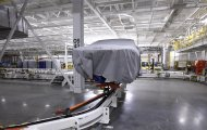 <p> FILE - In this Tuesday, July 16, 2013, file photo, a covered vehicle sits in part of the new paint shop at Chrysler's Sterling Heights Assembly Plant in Sterling Heights, Mich. The Commerce Department reports on wholesale prices for July on Wednesday, Aug. 14, 2013. (AP Photo/Paul Sancya, File)