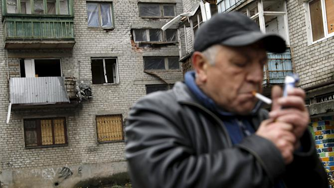 A man lights a cigarette near a residential building that was damaged during battles between Ukrainian armed forces and Russian-backed separatists, in Donetsk