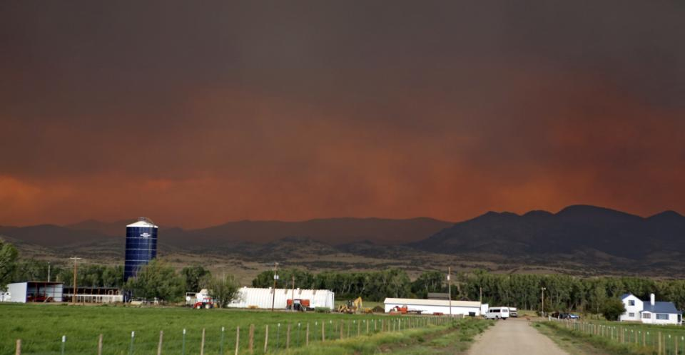 The smoke in the sky over a ranch near South Fork, Colo., glows red from a wildfire that is threatening the town on Friday, June 21, 2013. South Fork was evacuated Friday as the fire approaches from the west. (AP Photo/Ed Andrieski)