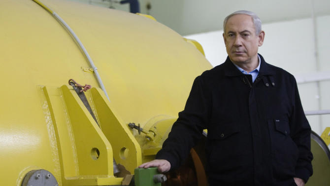 FILE In this Jan. 8, 2013 file photo, Israeli Prime Minister Benjamin Netanyahu visits the electronic accelerator lab in the Ariel University Center which had recently been formally upgraded to university status, becoming the first university in the West Bank Jewish settlements. A strikingly apocalyptic tone has emerged in Israel's hitherto muted election season, with opposition leaders and others desperately warning that a few more years of rule by Prime Minister Benjamin Netanyahu's heavily favored right wing might actually destroy the Jewish state. (AP Photo/Dan Balilty, Pool, File)