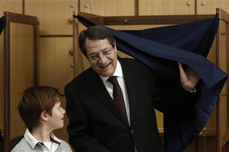 Cyprus presidential candidate Anastasiades, of the right wing Democratic Rally party, leaves a booth as his grandson Andis looks on at a polling station in Limassol