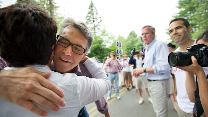 Republican presidential candidate Perry, hugs the daughter of Republican presidential candidate Bush as Bush looks on before participating in the Independence Day parade in Amherst, New Hampshire