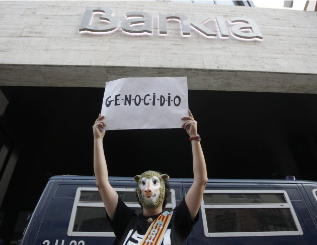 A protester holds a sign which reads &quot;Genocide&quot; in front of the Bankia headquarters during a demonstration in Valencia