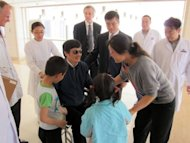 Chinese dissident Chen Guangcheng greets his wife Yuan Weijing (R) and children in Beijing, US ambassador to China Gary Locke looks on