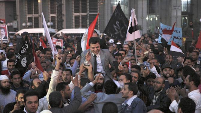Supporter of Egyptian President Mohammed Morsi cheer for Walid el-Sharabi, center, spokesman of the Coalition of Judges for Egypt, during a rally in front of Cairo University, Cairo, Egypt, Saturday, Dec. 1, 2012.  More than 100,000 Islamists waved Egyptian flags and hoisted portraits of President Mohammed Morsi in rallies nationwide Saturday to support his efforts to rush through a new draft constitution despite widespread opposition by secular activists and some in the judiciary. The rally, organized by the Muslim Brotherhood, is seen as a test of strength for Islamists seeking to counteract large opposition protests held this past week by liberal and secular groups who the Brotherhood say do not represent the vast majority of Egyptians.  (AP Photo/Thomas Hartwell)