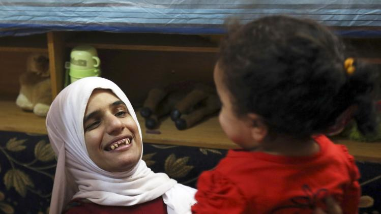 Sherien Fathy, a blind 32-year-old mother of two, plays with her daughter Rahma at their home in Cairo