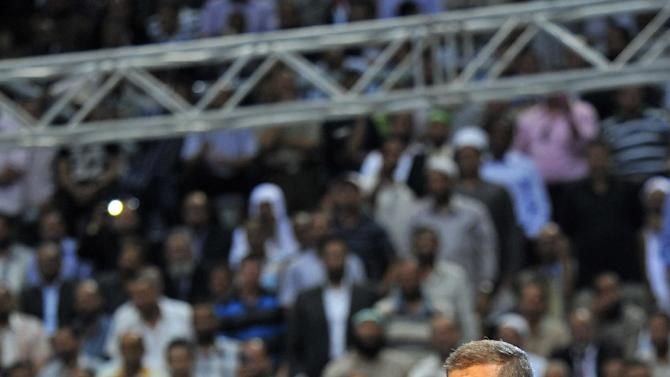 """In this image released by the Egyptian Presidency, Egyptian President Mohammed Morsi addresses a rally called for by hardline Islamists loyal to the Egyptian president to show solidarity with the people of Syria, in a stadium in Cairo, Egypt, Sunday, June 15, 2013. Egypt's Islamist president announced Saturday that he was cutting off diplomatic relations with Syria and closing Damascus' embassy in Cairo, decisions made amid growing calls from hard-line Sunni clerics in Egypt and elsewhere to launch a """"holy war"""" against Syria's embattled regime. (AP Photo/Egyptian Presidency)"""