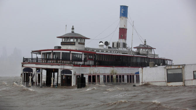 An historic ferry boat named the Binghamton is swamped by the waves of the Hudson River in Edgewater, N.J., Monday, Oct. 29, 2012, as Hurricane Sandy lashes the East Coast. Hurricane Sandy continued on its path Monday, as the storm forced the shutdown of mass transit, schools and financial markets, sending coastal residents fleeing, and threatening a dangerous mix of high winds and soaking rain.  (AP Photo/Craig Ruttle)