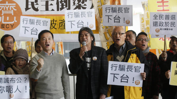 """Leung Kwok-hung, also known as Long Hair, a member of the Legislative Council, center, stands with other pro-democracy members of Hong Kong's legislature and other protesters as they display placards reading """"Chief Executive, step down"""" outside the Legislative Council in Hong Kong Wednesday, Jan. 9, 2013. Lawmakers were making a symbolic attempt Wednesday to impeach Hong Kong's Beijing-backed leader, the latest sign of the widening gulf between the semiautonomous southern Chinese city and its political masters in Beijing. (AP Photo/Kin Cheung)"""