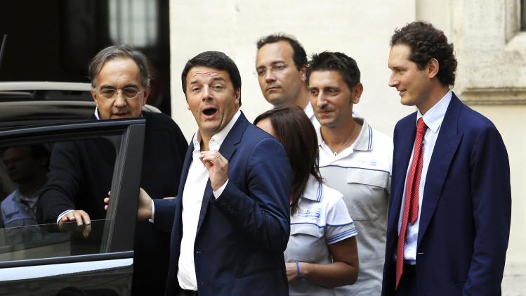 "Italian PM Renzi gestures during a meeting with Fiat Chairman Elkann and Chief Executive Marchionne to mark the presentation of new ""Jeep Renegade"" car at Chigi palace, in Rome"