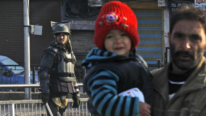 A Kashmiri civilian carries a child and walks past an Indian paramilitary soldier during curfew in Srinagar, India, Saturday, Feb. 9, 2013. A Kashmiri man Mohammed Afzal Guru, convicted in the 2001 attack on India's Parliament, has been hanged in an Indian prison, a senior Indian Home Ministry official said Saturday. On Saturday morning thousands of police and paramilitary troops had fanned out across Indian Kashmir anticipating that protests and violence might follow news of the execution. (AP Photo/Mukhtar Khan)