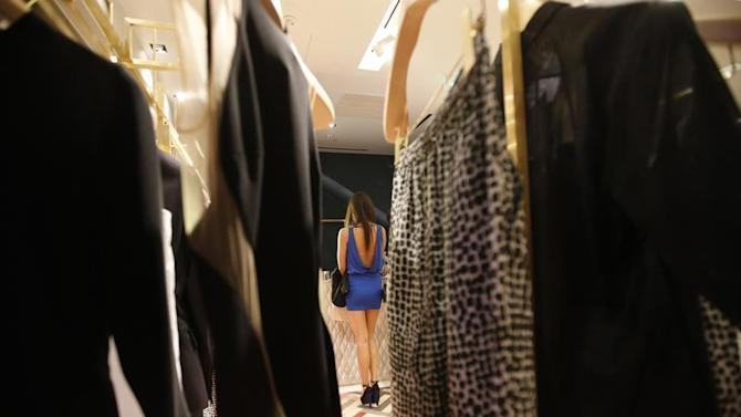 A woman pays for her purchases at a fashion accessory shop at a foreign luxury brand's boutique in Beijing