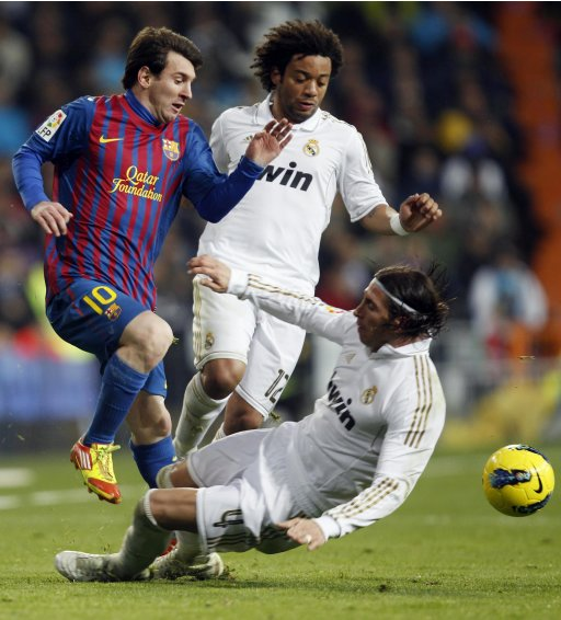Barcelona's Messi  is fouled by Real Madrid's Ramos as Real Madrid's Marcelo looks on during their Spanish first division soccer match in Madrid