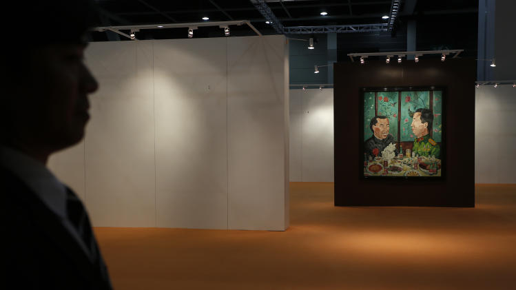 """A security guard stands next to a painting """" Revolutionary Family Series – Invitation to Dinner """" by Chinese artist Liu Wei at the Sotheby's autumn auction in Hong Kong Monday, Oct. 8, 2012. The work sold for US$2.24 million, set a world auction record for the artist. (AP Photo/Vincent Yu)"""