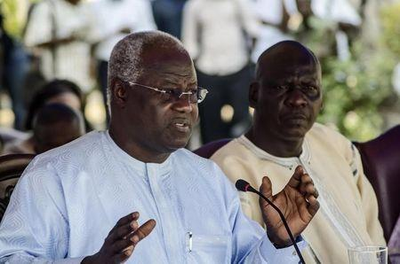 Gibson, the new mayor of Freetown, listens as Sierra Leone's President Koroma announces an operation in Freetown