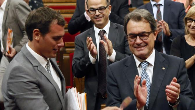 Catalonia's President Mas claps as Ciutadans's party leader Rivera gives him a sticker after a regional consultation law was approved at Catalonia's Parliament in Barcelona