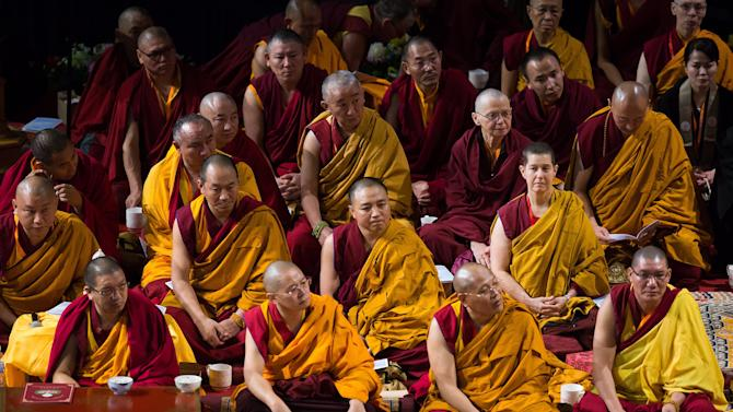 Buddhist monks listen as Tibetan spiritual leader the Dalai Lama speaks during a talk about teachings on empowerment and compassion as a path to inner happiness, at the University of British Columbia in Vancouver, British Columbia, on Thursday October 23, 2014. According to organizers proceeds from the event will support the British Columbia chapter of the Tibetan Resettlement Project, a humanitarian initiative to resettle 1,000 displaced Tibetans to Canada. (AP Photo/The Canadian Press, Darryl Dyck)