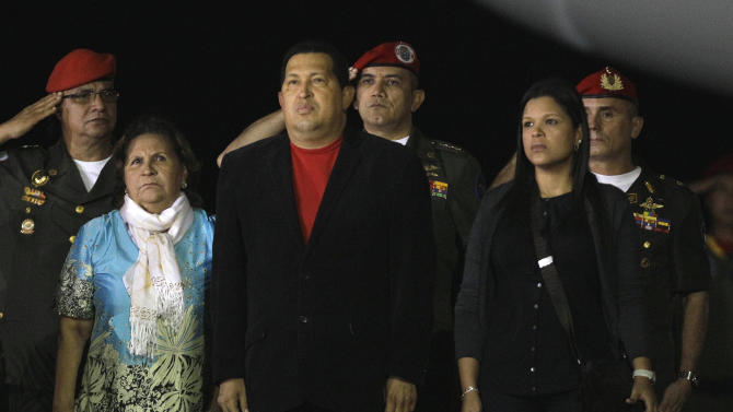 Venezuela's President Hugo Chavez, center front, stands with his mother Helena Frias, left, and daughter Maria Gabriela, right, during the playing of Venezuela's national anthem upon their arriving to the Simon Bolivar airport in Maiquetia, Venezuela, Friday March 16, 2012. Chavez, who traveled with family members from Havana, returned home Friday nearly three weeks after undergoing cancer surgery in Cuba. (AP Photo/Fernando Llano)