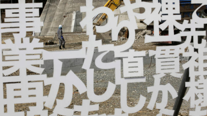 A worker walks behind a white plastic plate cutout of the words of a local businessperson, declaring determination to reopen the business, in a tsunami-stricken area in Minamisanriku, Miyagi prefecture, northern Japan, Monday, March 11, 2013. Japan marked the second anniversary on Monday of a devastating earthquake and tsunami that left nearly 19,000 people dead or missing. The words mean; I will restart my business from zero like my ancestor. (AP Photo/Shizuo Kambayashi)