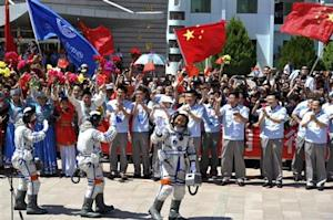 Chinese astronauts Wang , Zhang and Nie wave before leaving for the Shenzhou-10 manned spacecraft mission at Jiuquan satellite launch center in Jiuquan