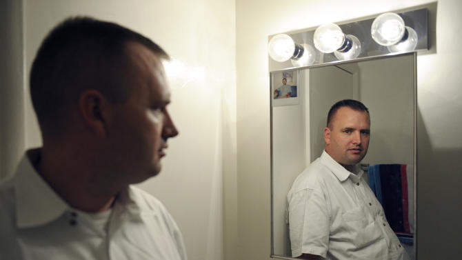 """In this Aug. 23, 2012 photo, Kevin Earley, 33, stands next to the medicine cabinet which has an old photo taped to it, in the bathroom of his Vienna, Va., apartment that he shares with a roommate. """"It reminds me to take my medicine every day and reminds me of where I have been and what I have been through,"""" said Earley, who works full time as a peer counselor, helping others with severe mental illnesses. (AP Photo/Cliff Owen)"""