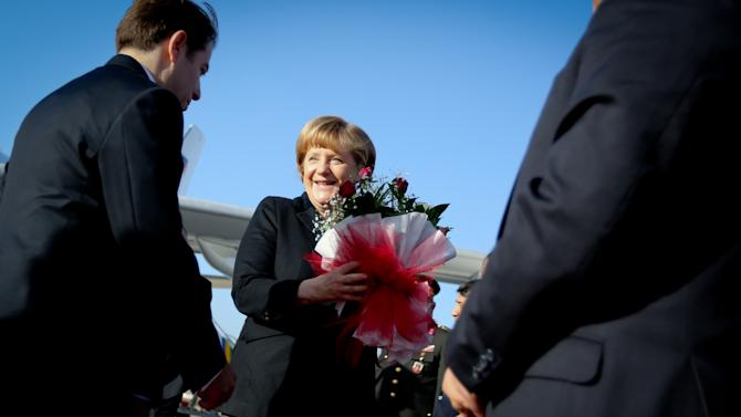German chancellor Angela Merkel is received by unidentified officials  in front of the German Air Force Airbus A340 aircraft at the airport in Gaziantep, Turkey, Sunday Feb. 24, 2013. Merkel  plans to visit  German soldiers deployed in Kahramanmaras, Turkey,  to protect  together with US and Dutch units, NATOpartner Turkey from possible missile attacks from Syria. (AP Photo/dpa, Kay Nietfeld)