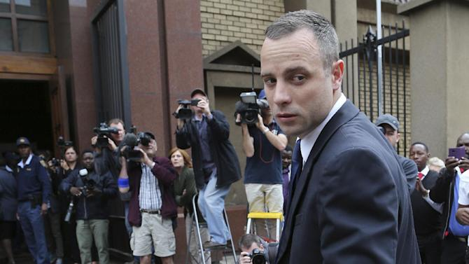 Oscar Pistorius looks back as he arrives at the high court in Pretoria, South Africa, Tuesday, May 6, 2014. Using witness accounts of a panicked nighttime phone call from Pistorius begging for help and his desperate pleas for Reeva Steenkamp to stay alive, the defense at his murder trial tried to reinforce its case Monday that the double-amputee Olympian fatally shot his girlfriend in a tragic error of judgment. (AP Photo/Themba Hadebe)