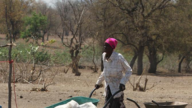 An elderly woman arrives to collect her monthly food ration at a distribution center in rural Mupinga area in Chiredzi, Zimbabwe