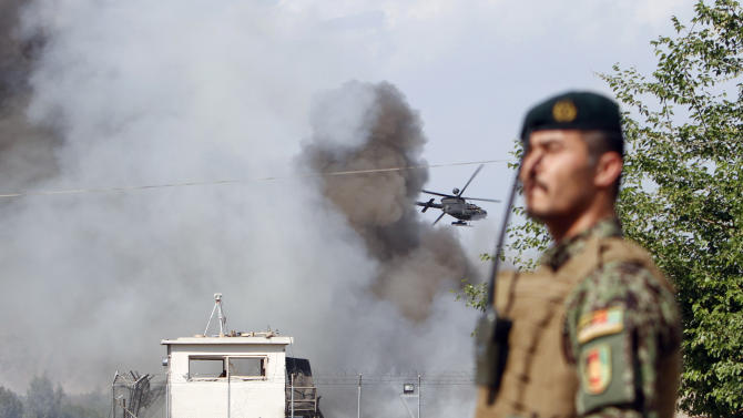 An Afghan soldier stands guard as a helicopter flies low over the scene of a suicide attack on the U.S.-led provincial reconstruction team (PRT) compound in the Behsood district of Jalalabad, east of Kabul Afghanistan, on Sunday, April 15, 2012. The Taliban launched a series of coordinated attacks on at least seven sites across the Afghan capital on Sunday, targeting NATO headquarters, the parliament and diplomatic residences. Militants also launched near-simultaneous assaults in three other eastern cities. (AP Phot/Rahmat Gul)