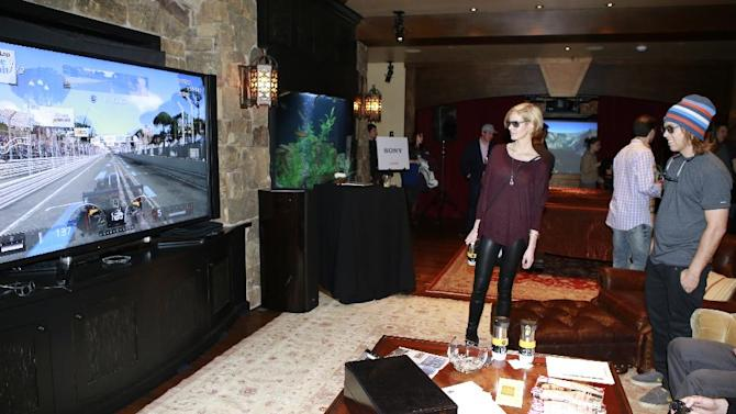 """IMAGE DISTRIBUTED FOR RAND LUXURY - Whitney Pratt, left, and Kevin Pearce from the film """"The Crash Reel"""" watch a game on a Sony 84-inch 4k Television at Resorts West House of Luxury, on Monday, Jan. 21, 2013 in Deer Valley, Utah. (Photo by Benjamin Cohen/Invision for Rand Luxury/AP Images)"""